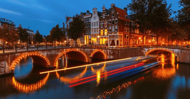 Canal iluminando à noite em Amsterdã